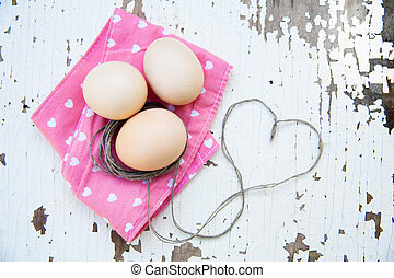 Top view of three eggs on rose napkin