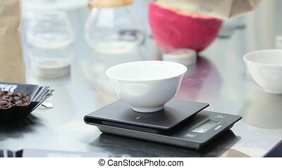 Coffee beans are weighed on kitchen electronic scales