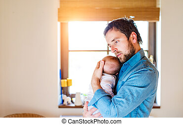 Young father holding his newborn baby son in his arm