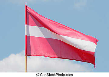 Flag of Latvia weaving against blue sky
