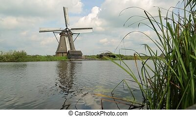 Windmill on the lakeside - Old windmill spinning in the wind