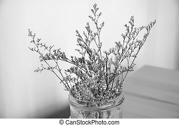 Black and White of Cutter flowers in glass on the wooden...