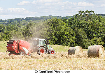 Farmer baling dried grass for hay with a tractor and baler, two bales at the side
