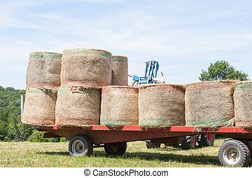 Loading and stacking round hay bales on a trailer for transport