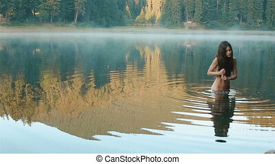 Young beautiful naked mermaid in the picturesque mountain...