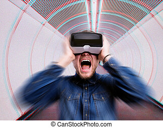 Man wearing virtual reality goggles, standing in corridor -...