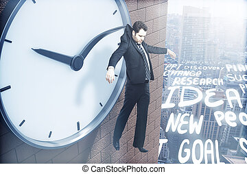 Time management concept with businessman hanging on clock...