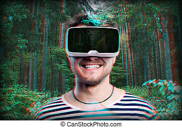 Man wearing virtual reality goggles. Green forest. - Hipster...