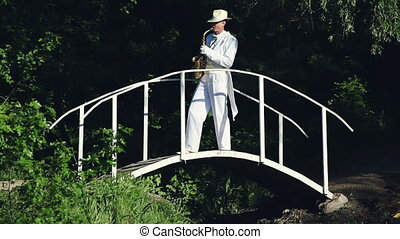 Saxophonist in a white frock coat and hat playing on the...