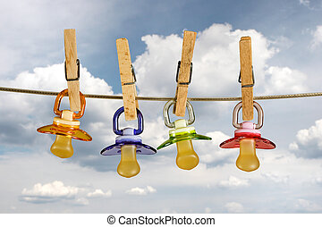 Pacifiers in line - Colored baby pacifiers hanging outside...