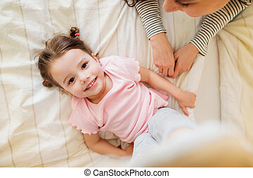 Mother and daughter lying on bed in parents bedroom - Mother...