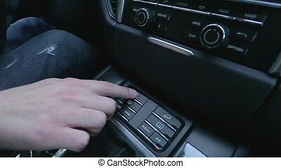 Man presses button on car's dashboard