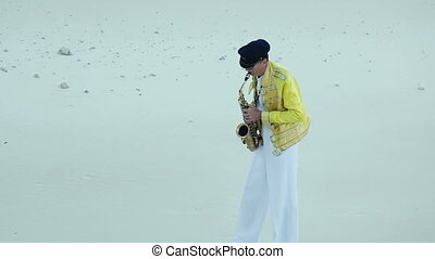 Saxophonist. Actor in a scenic suit playing in the sand pit....