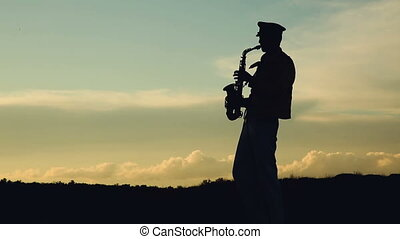 Saxophonist. Man playing on saxophone against the background...