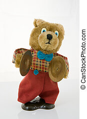 Wind-up teddy bear with brass cymbals, isolated against a...
