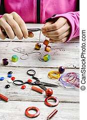 bead decoration handmade - Hands with pair of pliers in the...