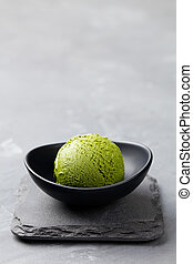 Green tea matcha ice cream scoop in bowl on a grey stone background. Copy space