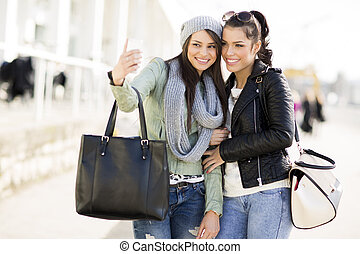 Young women takin selfie outdoor - Two young women have fun...