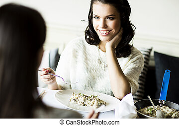 Women at the table in the restaurant - wo young women...