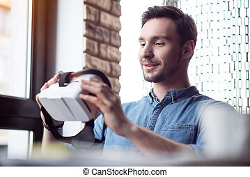 Pleasant man using virtual reality device - Smart...