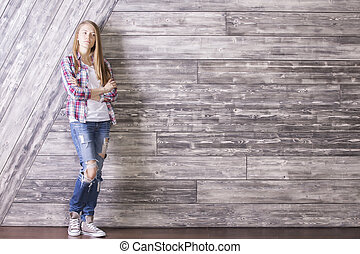 Thinking girl against wooden wall - Casually dressed young...