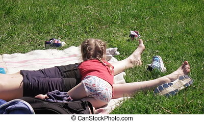 Girl with her mother on picnic - On carpet is mother and...