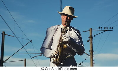 Saxophonist, male, middle-aged man standing on the railway...