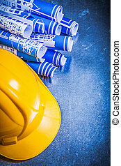 Blue construction drawings yellow building helmet on...