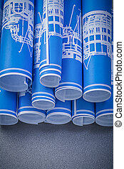 Set of blue rolled engineering drawings on grey background...