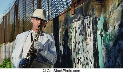 Saxophonist against a wall with graffiti and power lines...