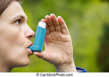 Asthma patient inhaling medication for treating shortness of...