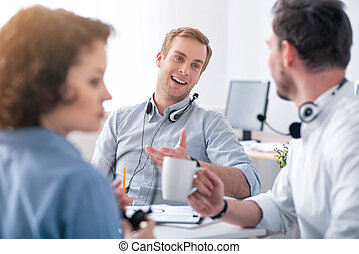 Pleasant colleagues talking at the table - Exchange your...