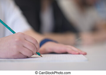 male student taking notes in classroom