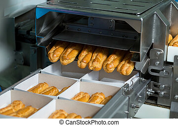 Boxes with eclairs on conveyor.