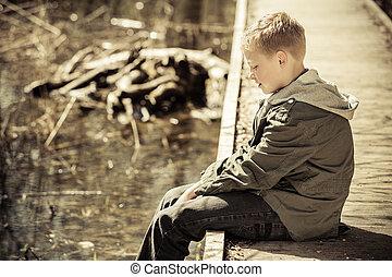 Single boy in jacket sitting on dock - Long telephoto side...