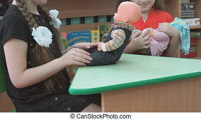 Two little girl playing in the small doll on a green table...