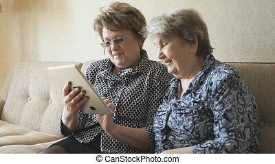 The old woman and her friend looking at photos