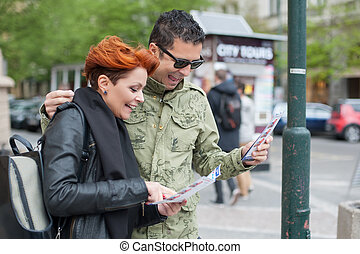 Couple of tourists looking at city guide - Happy couple of...