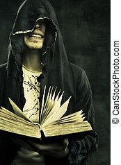 Dark omen - Portrait of sinister prophet in hood holding...