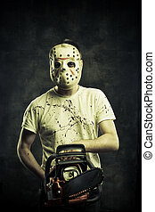 Scary mad maniac in mask with bloody chainsaw