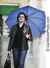 woman on street with umbrella - one young happy woman...