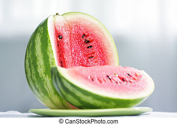 Cut watermelon - Cut striped watermelon laying on green...