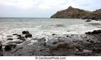 Beach and ancient crumbling mountains of Crimea - Sea waves...