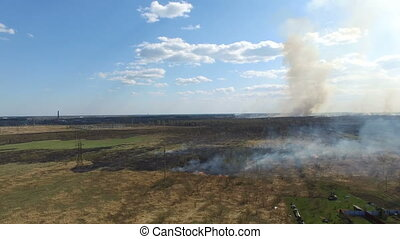 Burning grass near village. Aerial footage