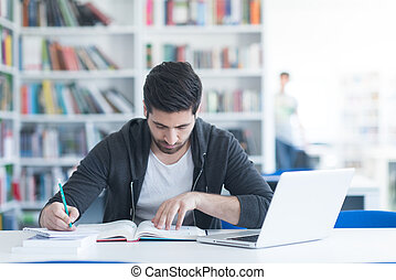 student in school library using laptop for research -...