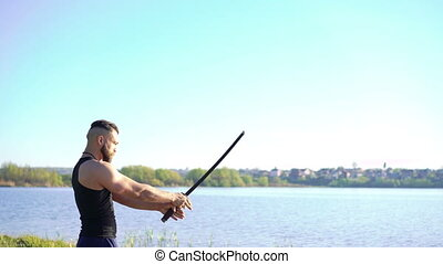 Demonstration of sword movements by master on the river background. 4k