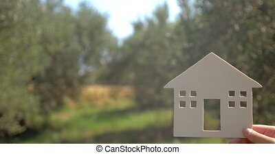 House In Hands On Natural Background - The house in hands on...