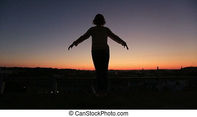 Silhouette of young woman raising hands to sun at sunset on back view. Moment of freedom and happines