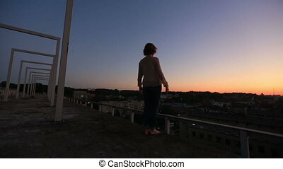 Silhouette of young woman raising hands to sun at sunset. Moment of freedom and happines. Young woman meditates on the bridge with city landscape background