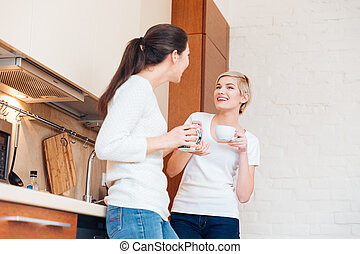 Two women gossiping on the kitchen